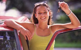 Happy student registered at City Driving School in Montreal is holding car keys proudly