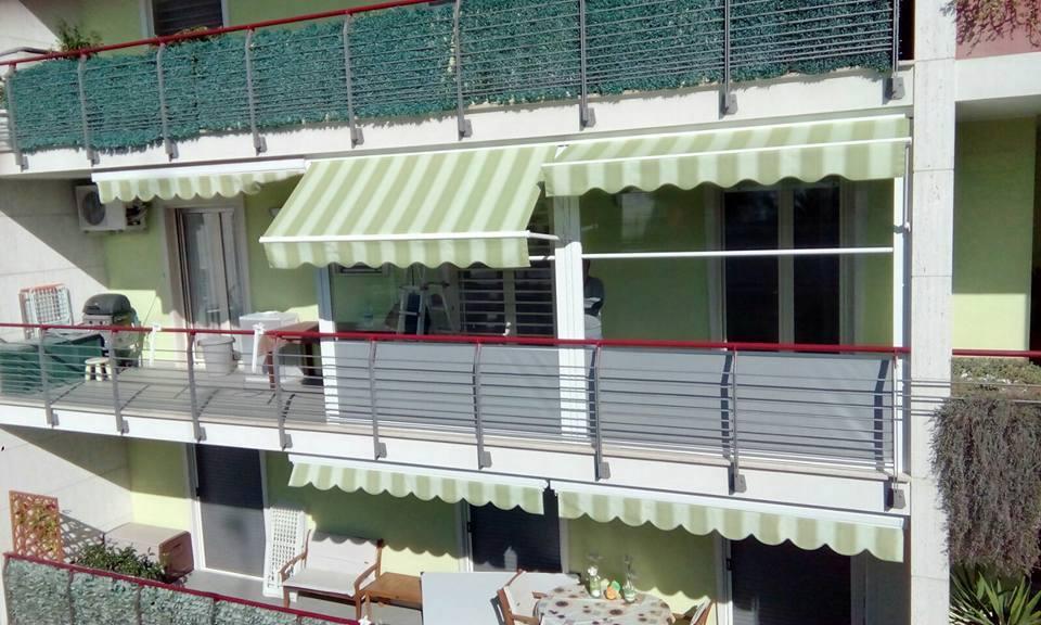 un balcone con un tendone bianco e verde