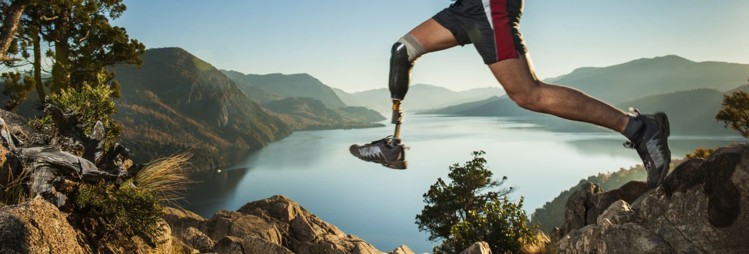 man wearing prosthetic devices running in mountains in Rochester, NY