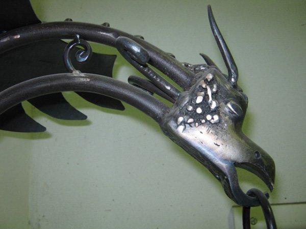 manufatto in ferro a forma di drago visto di profilo