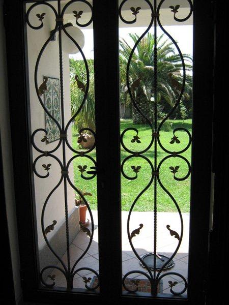 un serramento in ferro battuto  con vista del giardino all'esterno