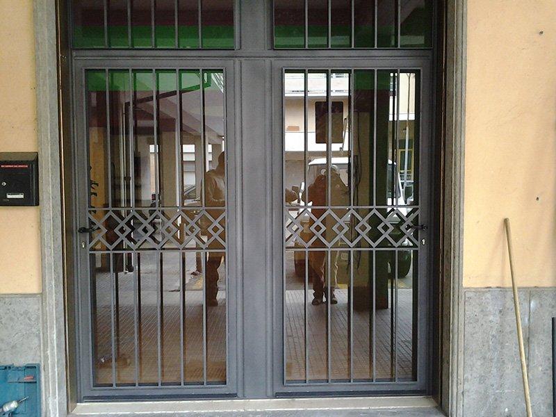 una porta d'entrata in vetro e ferro battuto
