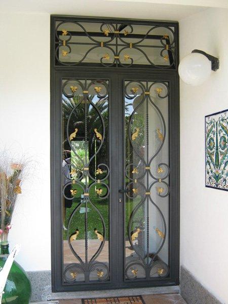 una porta in ferro battuto e vetro e vista del giardino fuori