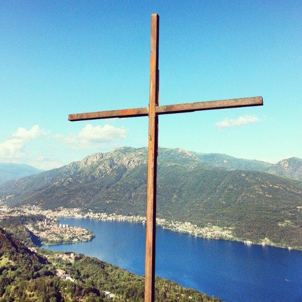 una croce di legno e dietro un paesaggio con vista del lago e delle montagne