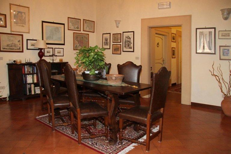 Tavola da pranzo di legno antica con sei sedie di legno e pelle, una piccola libreria e tabelle completano il soggiorno decorato con piante