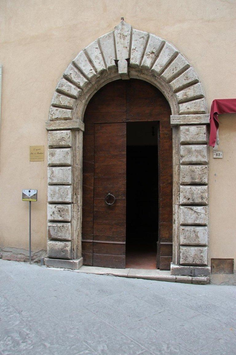 Antico arco di pietra dove si apre la vechia porte in legno massiccio della casa
