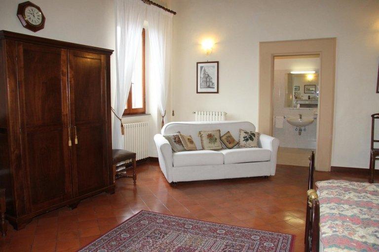 Angolo della camera da letto con un sofà bianco di pelle