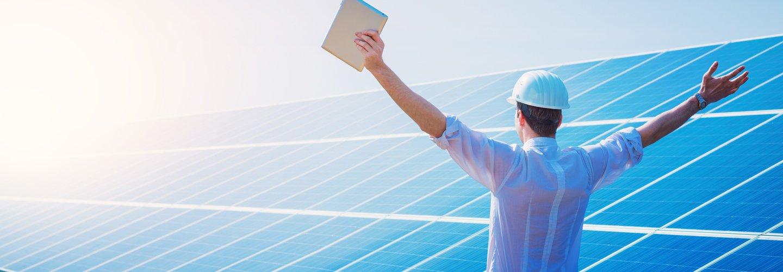 Uomo con le braccia aperte all'impianto solare termico