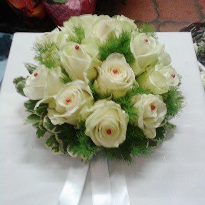 Una scatola di color bianco con sopra un bouquet di rose bianche