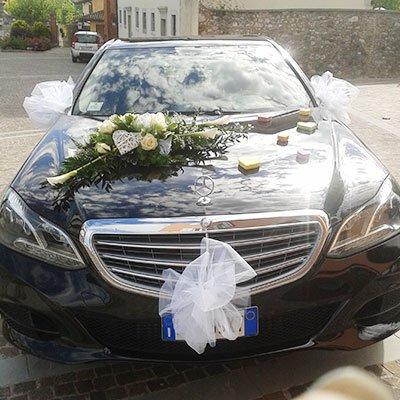 Una macchina nera con fiocchi bianchi e sopra un bouquet di rose bianche