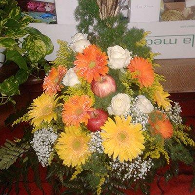 Un bouquet di fiori di color arancioni, giallo,rose bianchi e due mele messe insieme dei fiori