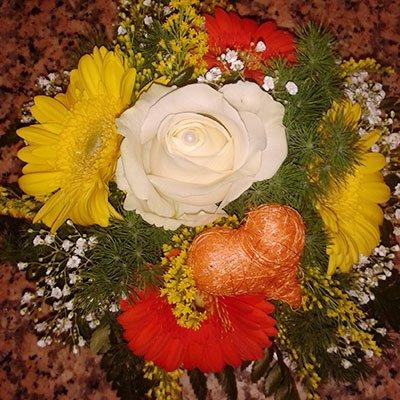 Un bouquet di fiori di color arancioni, giallo e rose bianchi