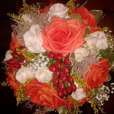 Un bouquet delle rose di color bianche e arancione e dei peperoncini messi insieme dei fior
