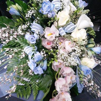 Un bouquet di fiori di color azzurro, bianco e rosa