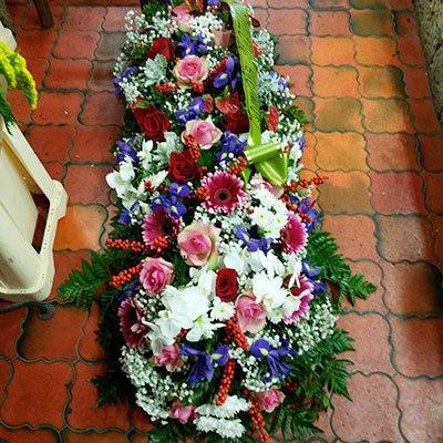 Un bouquet lungo delle rose di color rosa, rosso, bianco e alcuni fiori di color blu