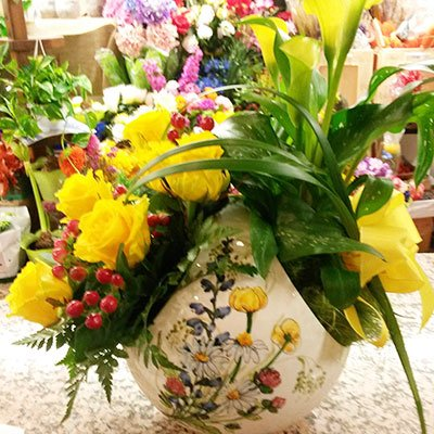 Un vaso di ceramica con rose gialle e altri fiori gialli