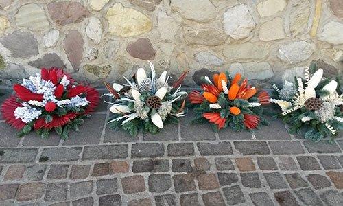 Vari bouquet con foglie colorati e altri decorazioni appoggiati su un pavimento