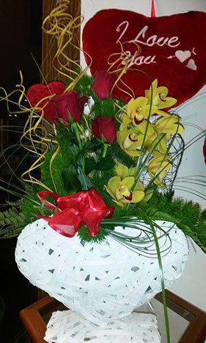 Un mazzo di fiori orchidea di color giallo, rose di color rosso e dei cuoricini  con uno scritto I love you