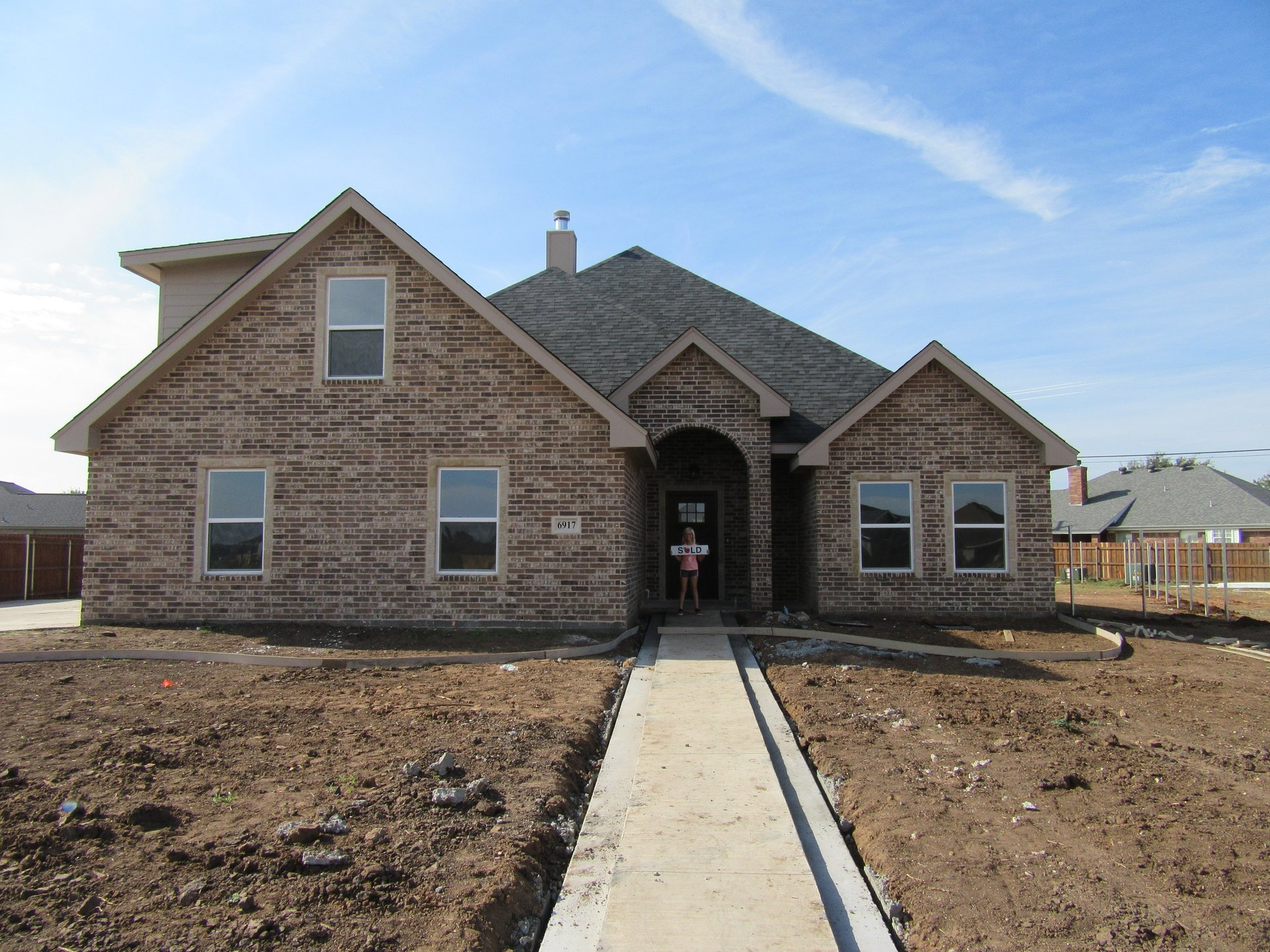 buyer posing in front of new home built by cornerstone custom homes