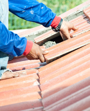 Man fitting new roof tiles