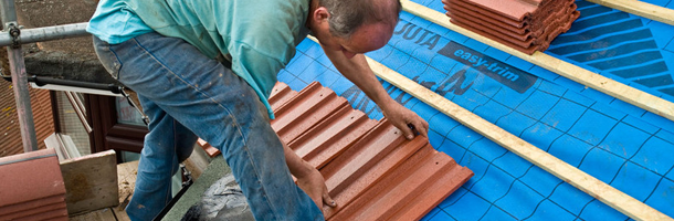 A man fitting new slate roof tiles