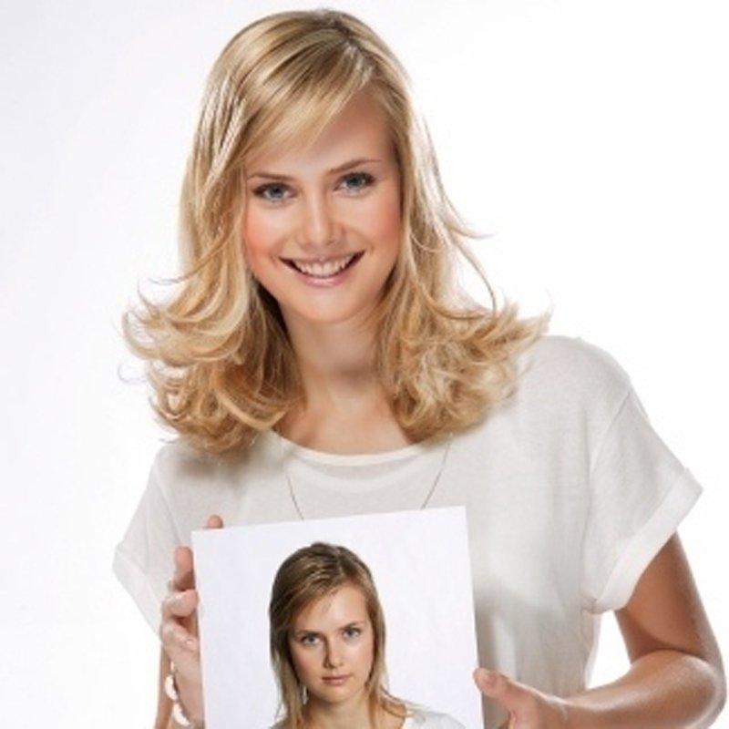 ragazza bionda sorridente con una foto in mano