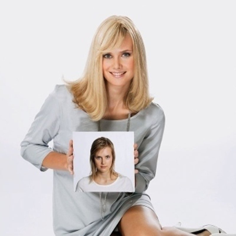 ragazza bionda sorridente con una foto in mano con sfondo grigio