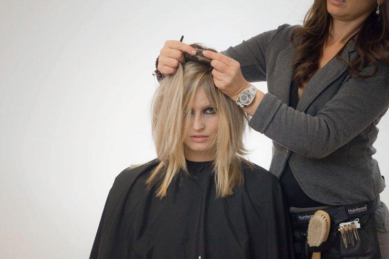 parrucchiere mentre taglia capelli di una donna