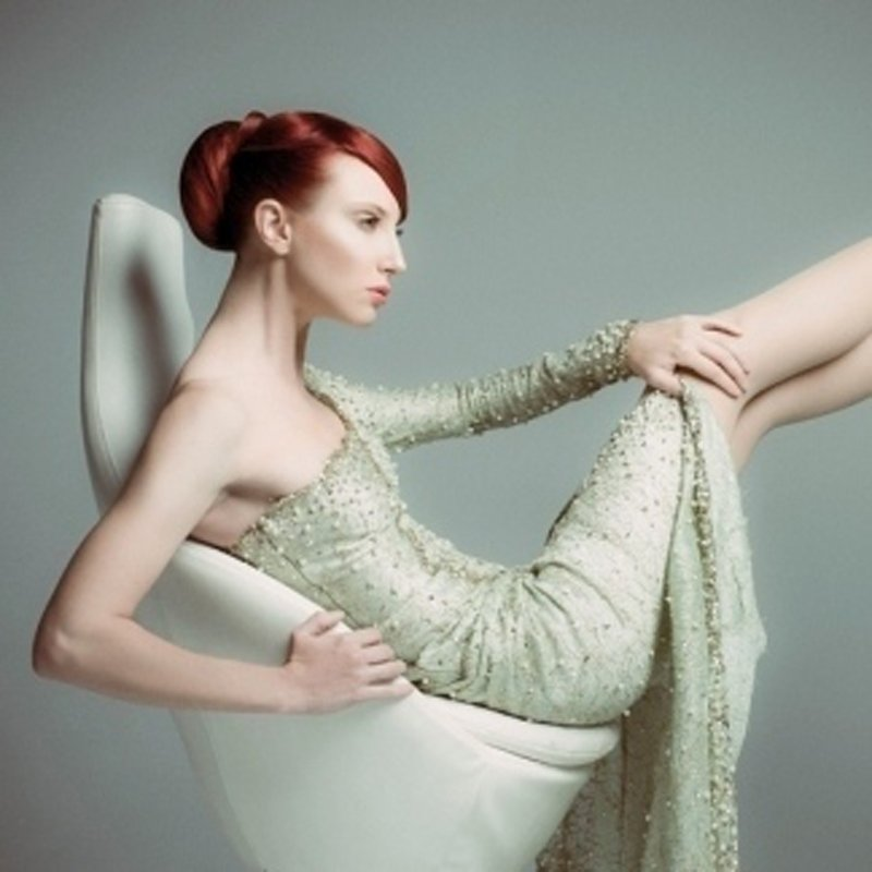 una modella con i capelli rossi seduta su una poltrona in stile
