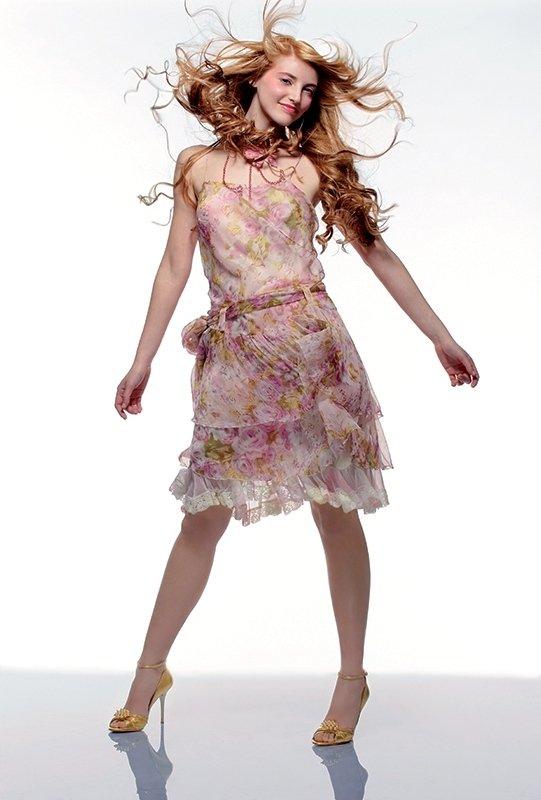 una ragazza con un abito bianco a fiori rosa e capelli mossi