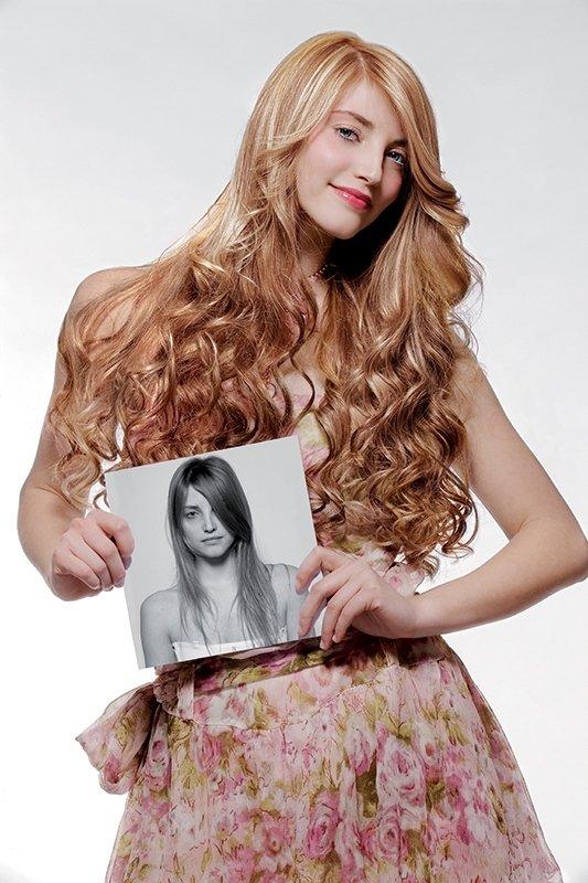 una ragazza bionda con capelli mossi che mostra una foto