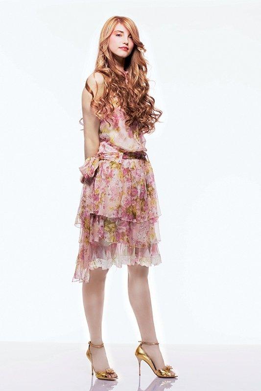 una ragazza bionda con capelli mossi e un abito bianco a fiori rosa