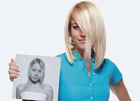 una ragazza con capelli biondo platino che coprono gli occhi mentre mostra una foto