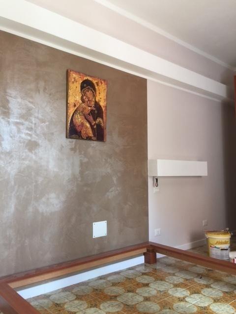parete con quadro della madonna e base del letto in legno