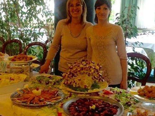 un buffet con i piatti serviti e due donne sorridente