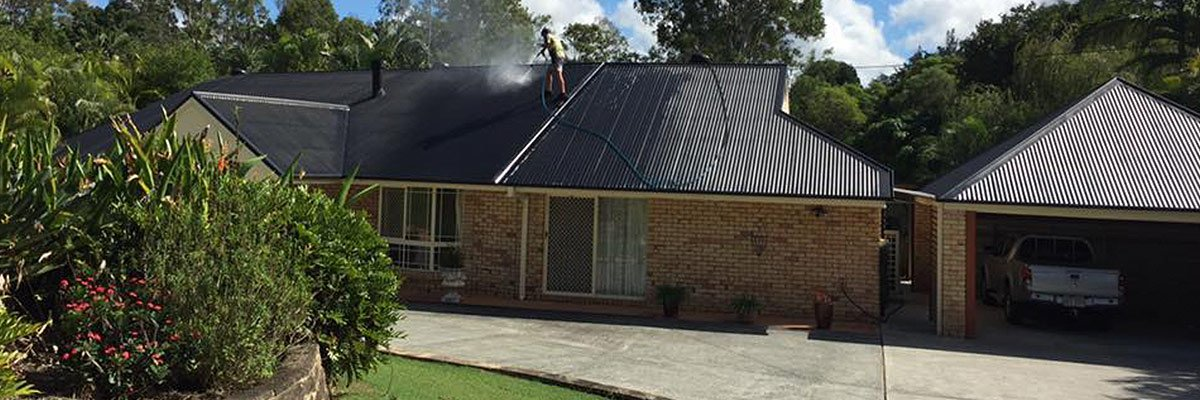 country wide roofing pty ltd worker cleaning old black tiles with water