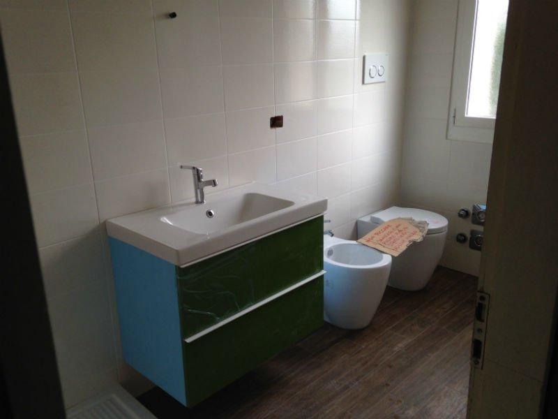 un lavabo con sotto un mobiletto verde, un bidet e un wc