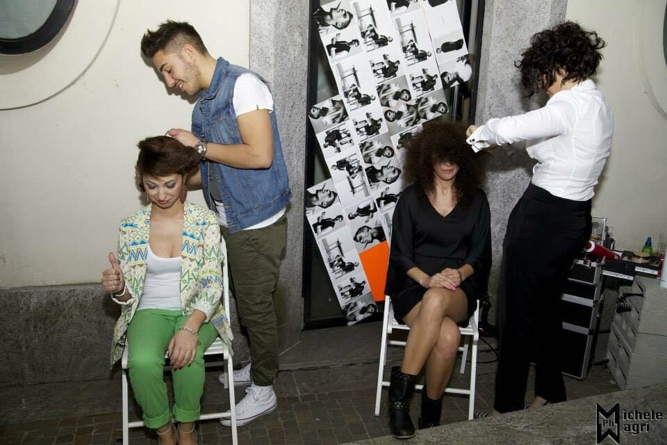 due parrucchieri realizzano l'acconciatura a due ragazze