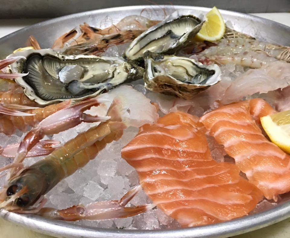 un vassoio con delle ostriche, scampi e filetti di salmone