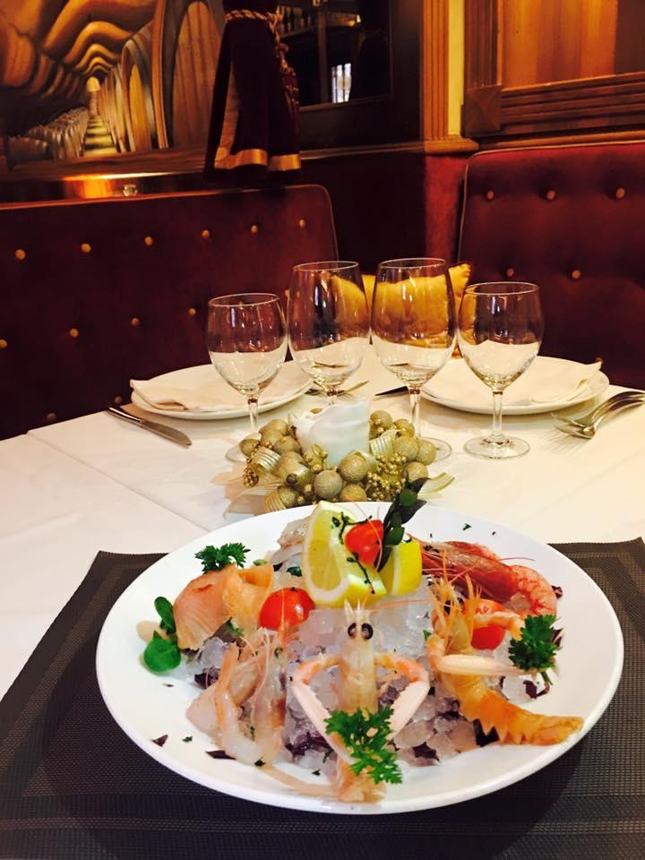 un tavolo apparecchiato e un piatto con degli scampi