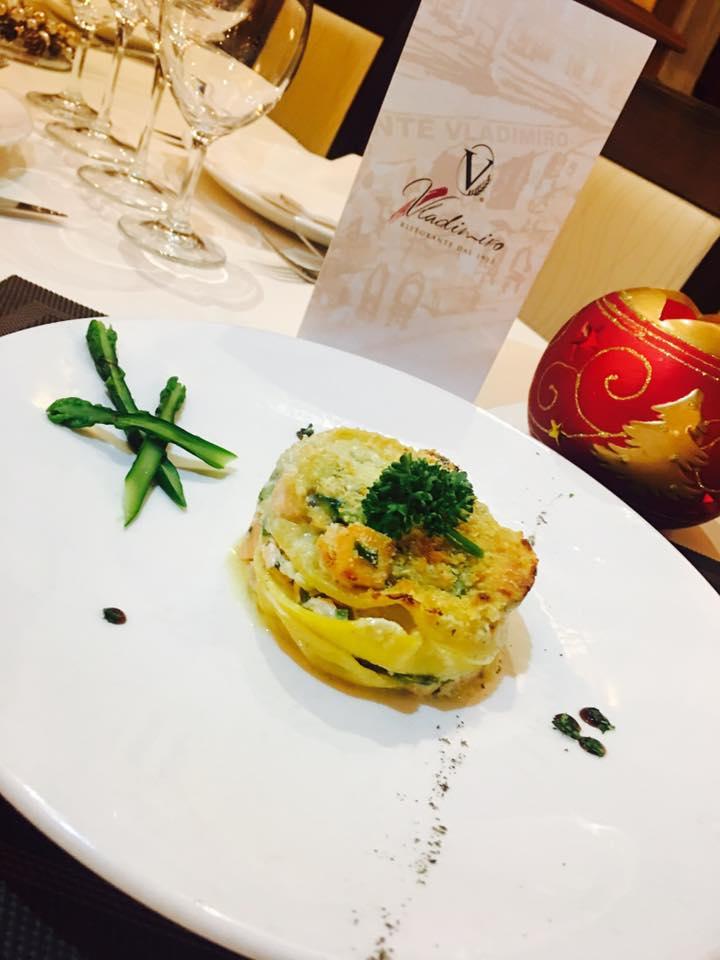 un tavolo con un piatto di lasagne e accanto degli asparagi