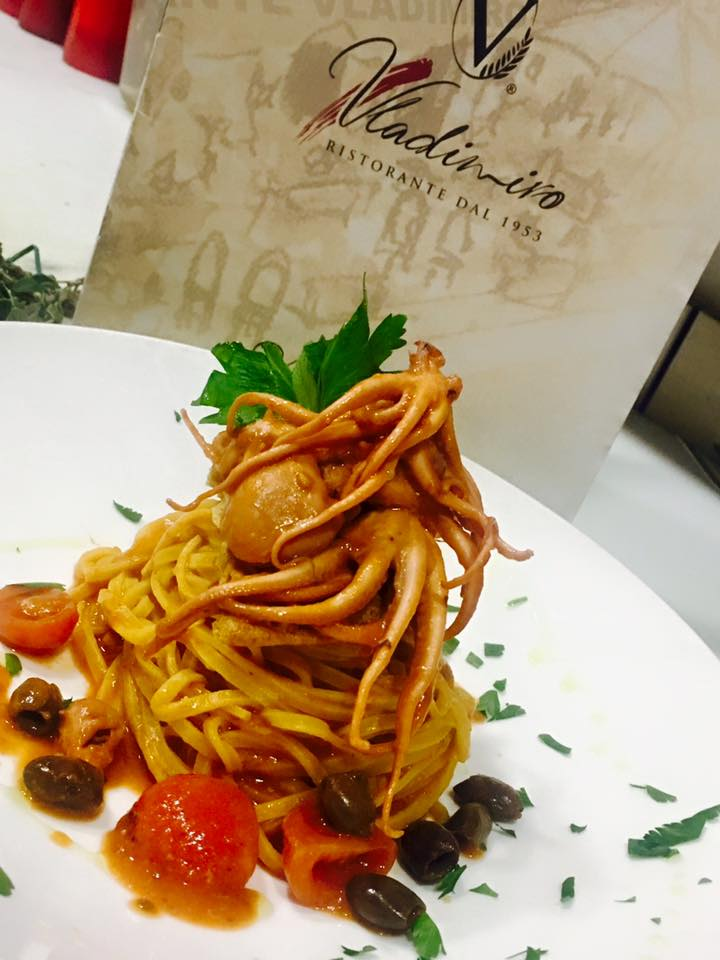 un piatto di linguine ai moscardini, pomodori e delle olive