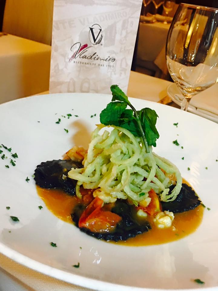 un piatto di ravioli al nero di seppia e pomodoro