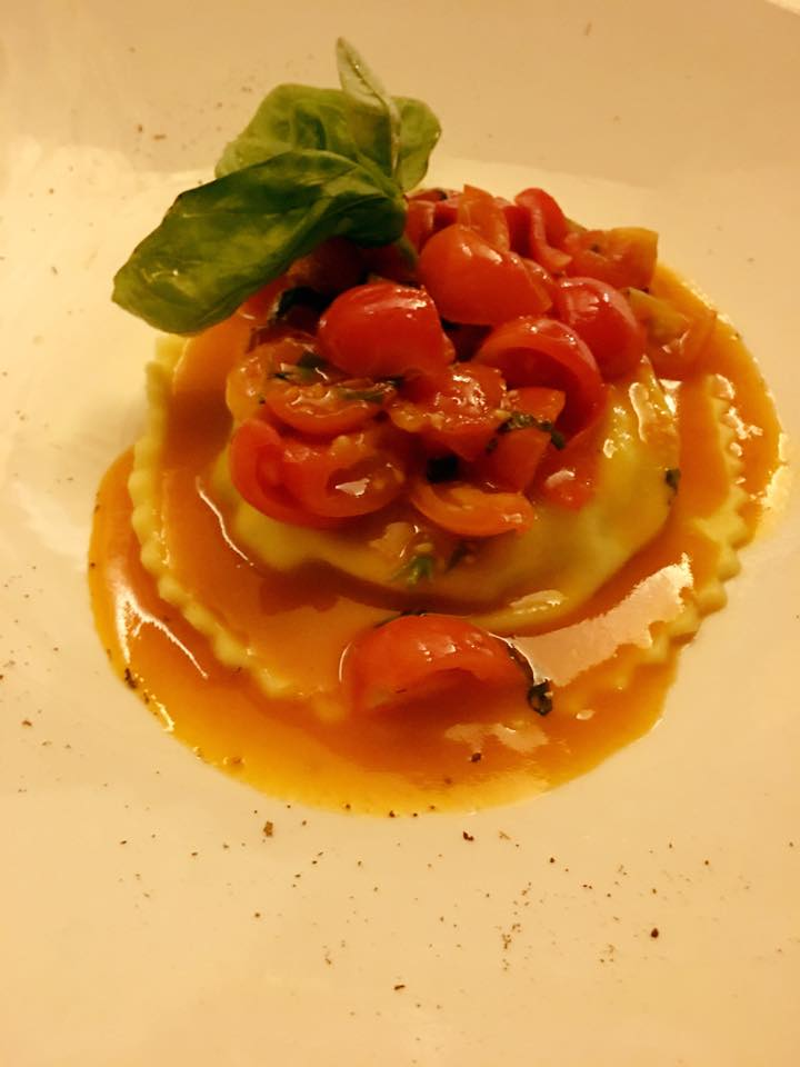 un piatto di ravioli ai pomodorini e basilico