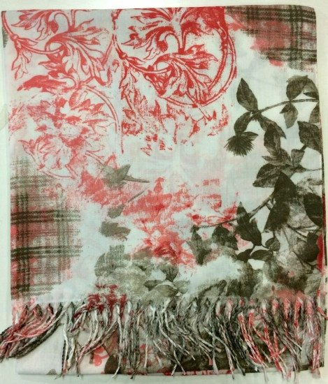Una sciarpa con disegni di color rosso e delle foglie verdi