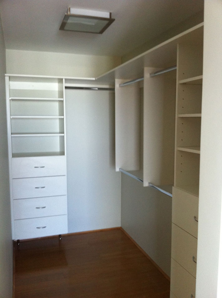 walk in wardrobe with white shelves and metal rods