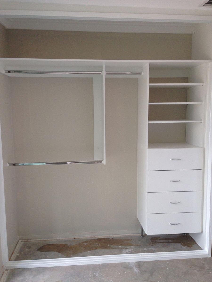 corner of white shelving to walk in wardrobe