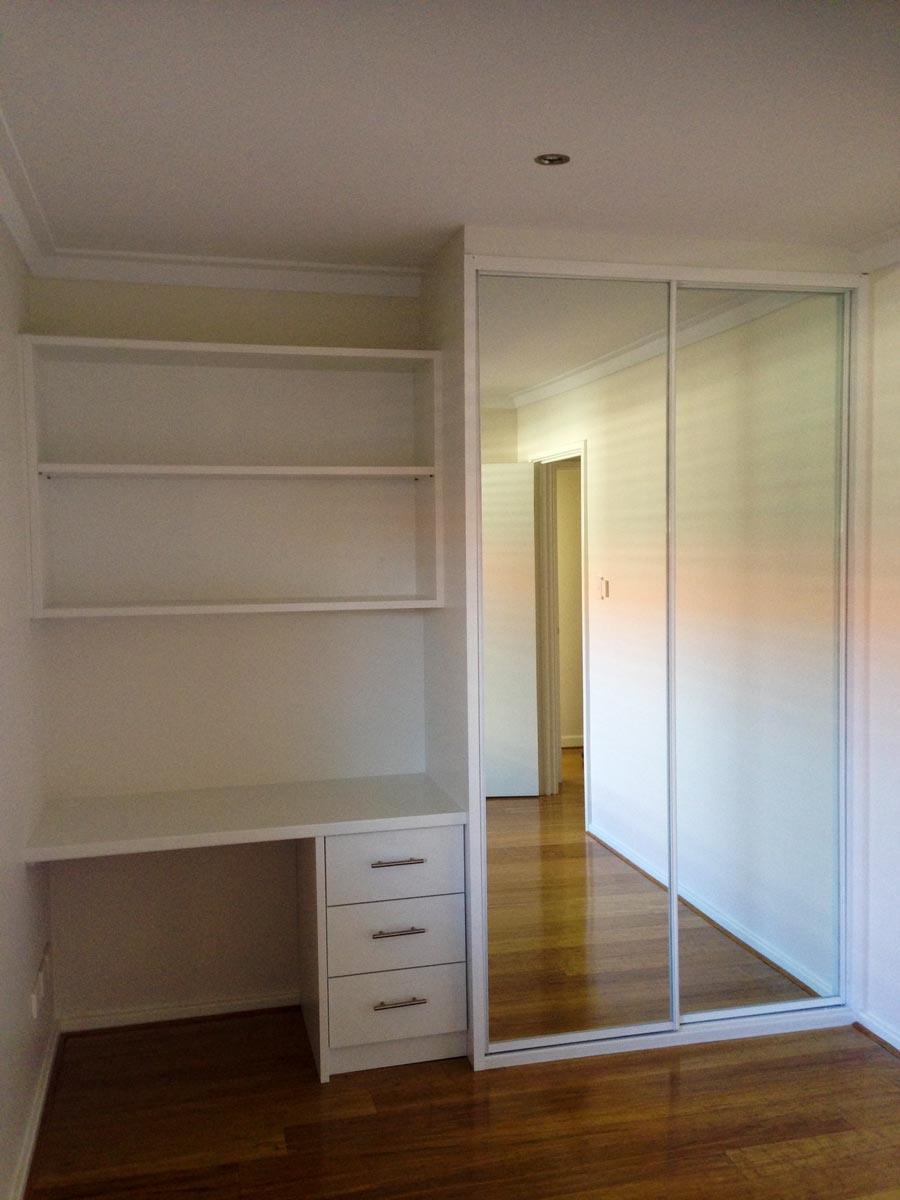 mirrored sliding wardrobe with white frame and desk to the left side