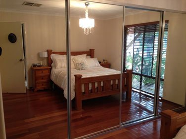 4 door sliding mirrored wardrobe with silver frame reflecting bed