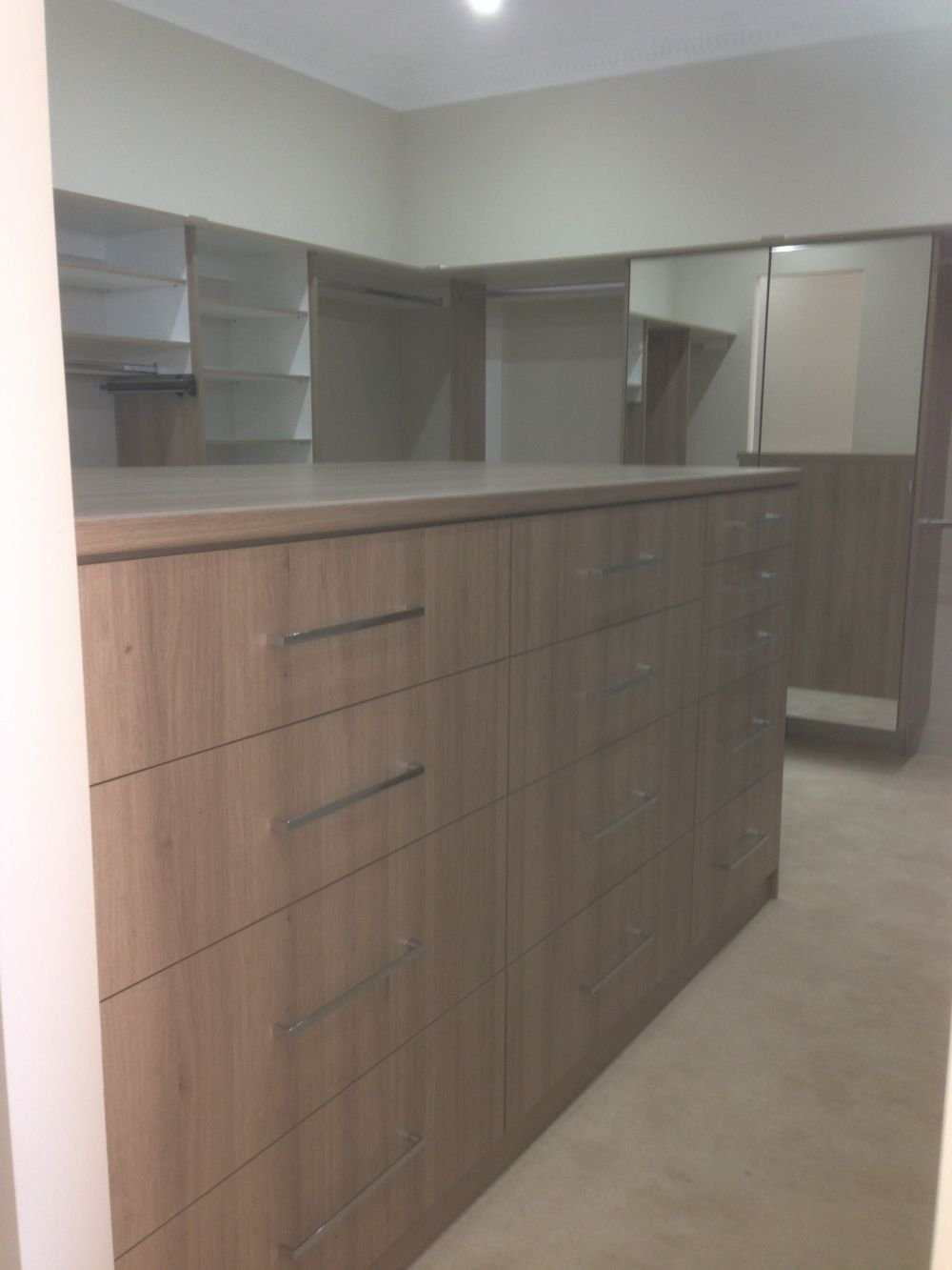 walk in wardrobe with dresser in the middle of room